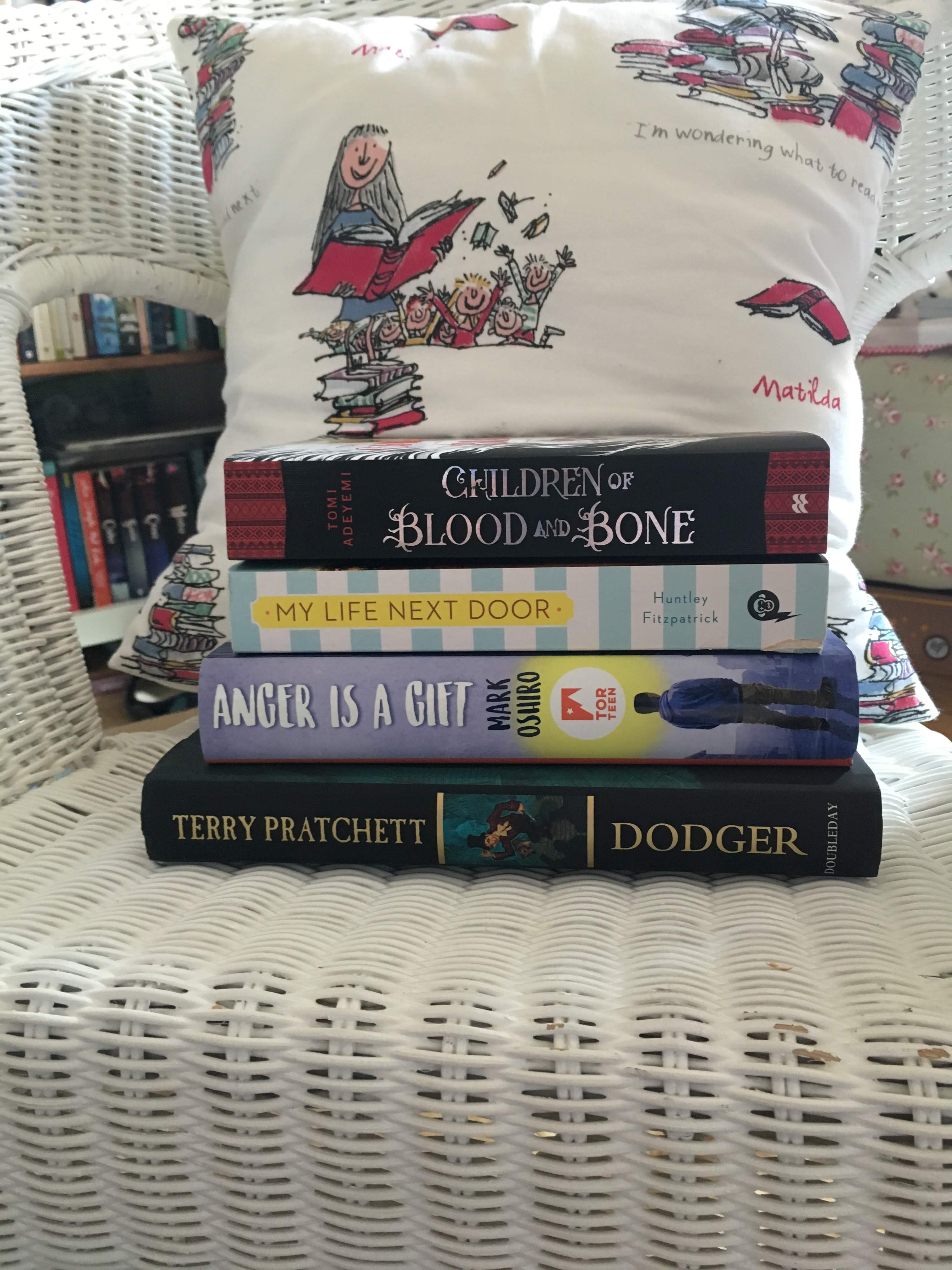"Colour photograph of a stack of books on a white wicker chair, with a cushion showing Roald Dahl's character Matilda on it. The stack of books is, top to bottom, ""Children of Blood and Bone"", ""My Life Next Door"", ""Anger is a Gift"", and ""Dodger""."
