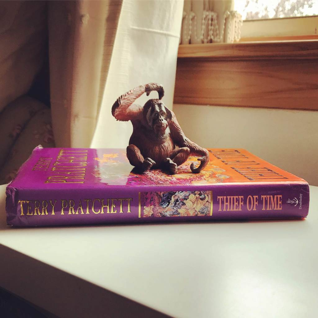 Colour photo - small orangutan ornament scratching its head sits atop a UK hardback of Thief of Time by Terry Pratchett.