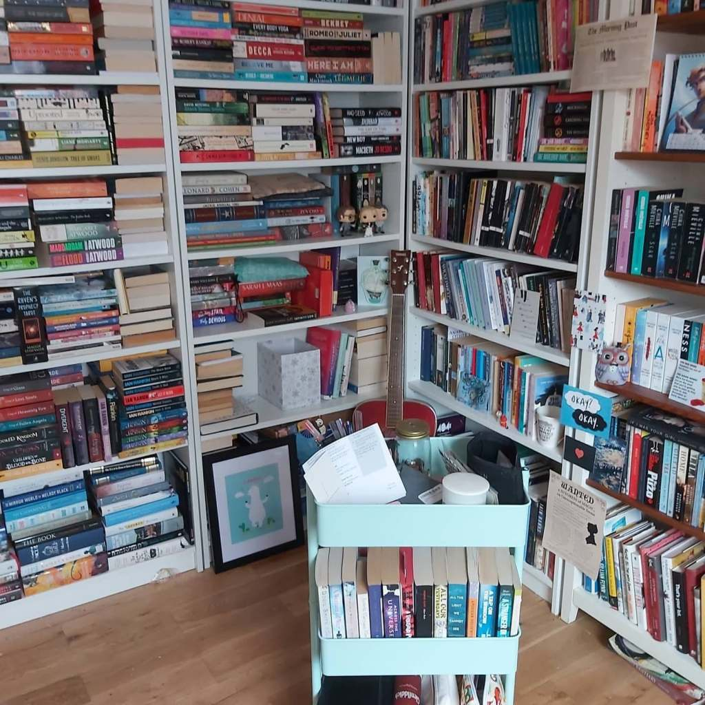 Photo of bookshelves with books stacked on the shelves, and a three-tier trolley in turquoise with books and stationery on it.